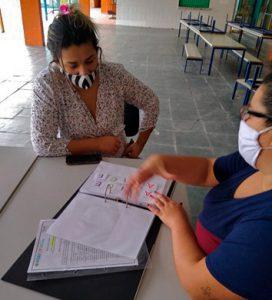 Mãe de estudante sentada à mesa com educadora, vendo atividades escolares em fichário. Ambas utilizam máscara. Fim da descrição.
