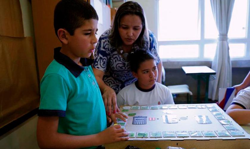 Estudante com deficiência visual manuseia Jogo da Trilha Interativo auxiliado por professora. Fim da descrição.
