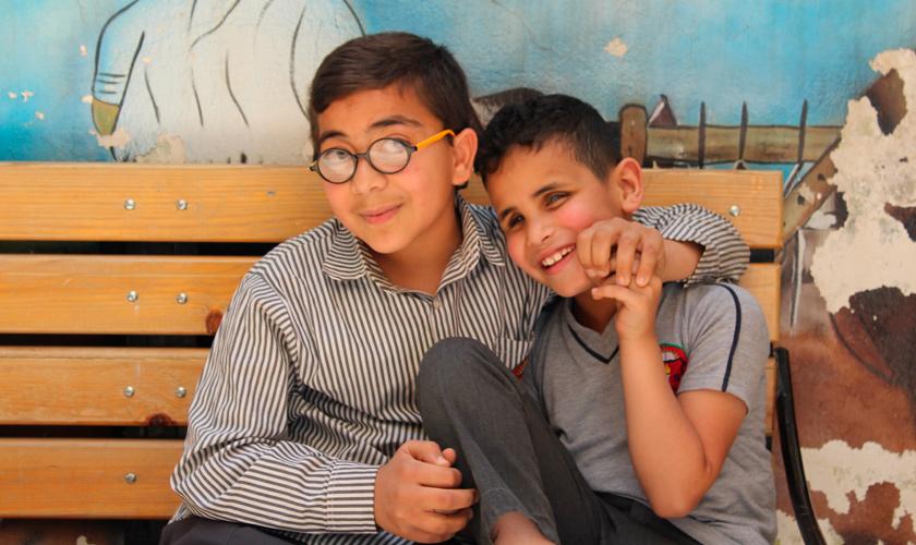 Dois estudantes, sentados em banco de madeira, se abraçam e sorriem para foto. Um deles está com óculos de grau e outro é cego. Fim da descrição.