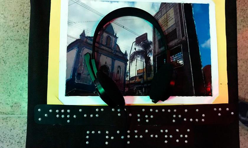 Imagem de fotografia de igreja local. Em cima da foto, um fone de ouvido para a audiodescrição. Abaixo da imagem, legenda em braile. Fim da descrição.
