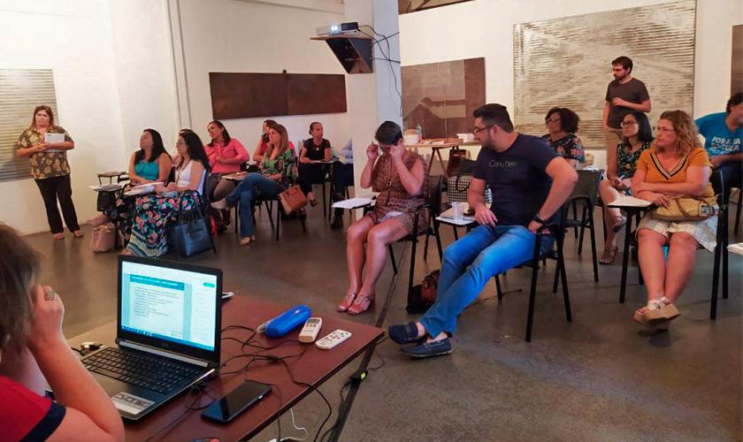 Representantes de municípios paulistas participam de formação. Eles estão sentados em duplas e, à sua frente, há uma mesa onde mulher usa notebook. Fim da descrição.