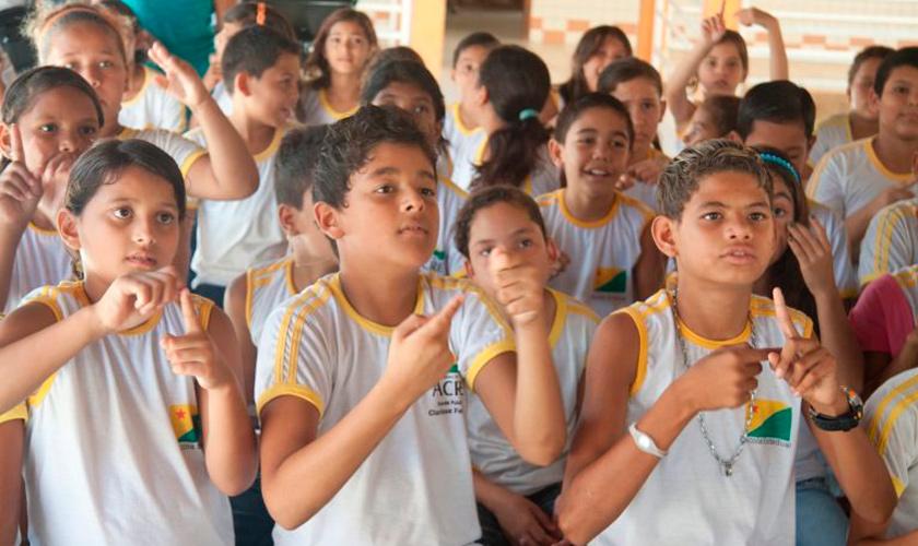Grupo de crianças com uniformes escolares faz sinais com as mãos durante aula de Libras.