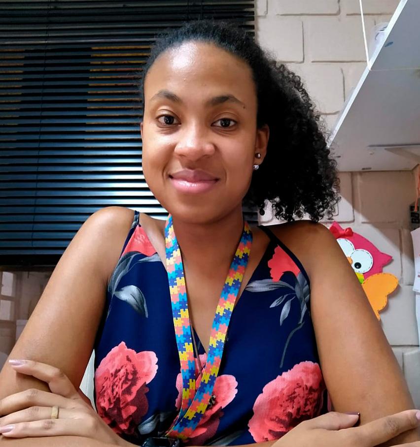 Natália Cesar de Brito, de braços cruzados, sorri para a câmera. Ela é uma mulher negra, usa o cabelo preso e veste uma blusa azul com flores rosas. Fim da descrição.