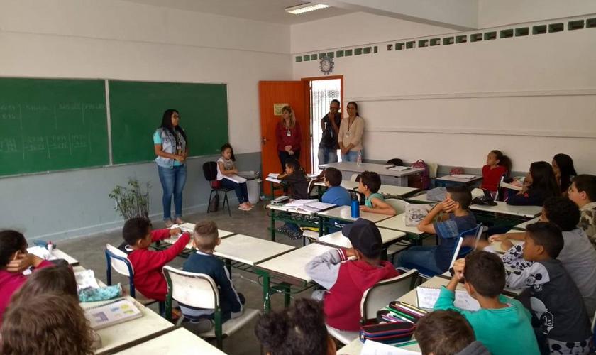 Em sala de aula, estudantes em carteiras dispostas em grupos. Três educadores estão de pé em frente à porta e uma professora está em frente à turma, com a lousa de fundo. Fim da descrição.