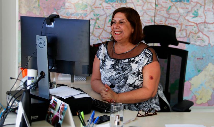 Silvia Grecco, mulher branca com cabelo castanho curto, sorri para a tela do computador à sua frente. Ela veste uma blusa branca com desenhos pretos. Ao fundo, mapa da cidade de São Paulo cobre toda a parede. Fim da descrição.