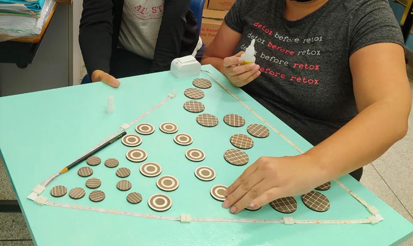 """Duas educadoras realizam a montagem do jogo """"A teia"""". Uma dela segura uma placa de madeira em verde claro, enquanto a outra posiciona círculos de diferentes tamanhos dentro de um retângulo posicionado no painel de madeira. Fim da descrição."""