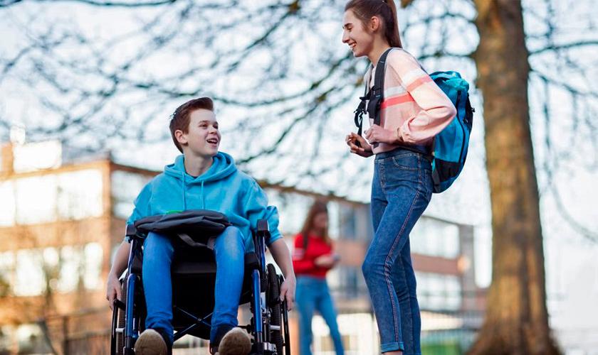 Dois estudantes, um em cadeira de rodas e a outra em pé, conversam e dão risada ao ar livre. Fim da descrição.