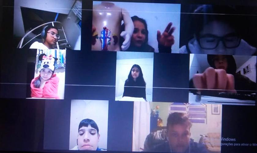 """Em videoconferência, sete estudantes observam material pedagógico """"Sistema excretor"""", apresentado por educadora. Fim da descrição."""