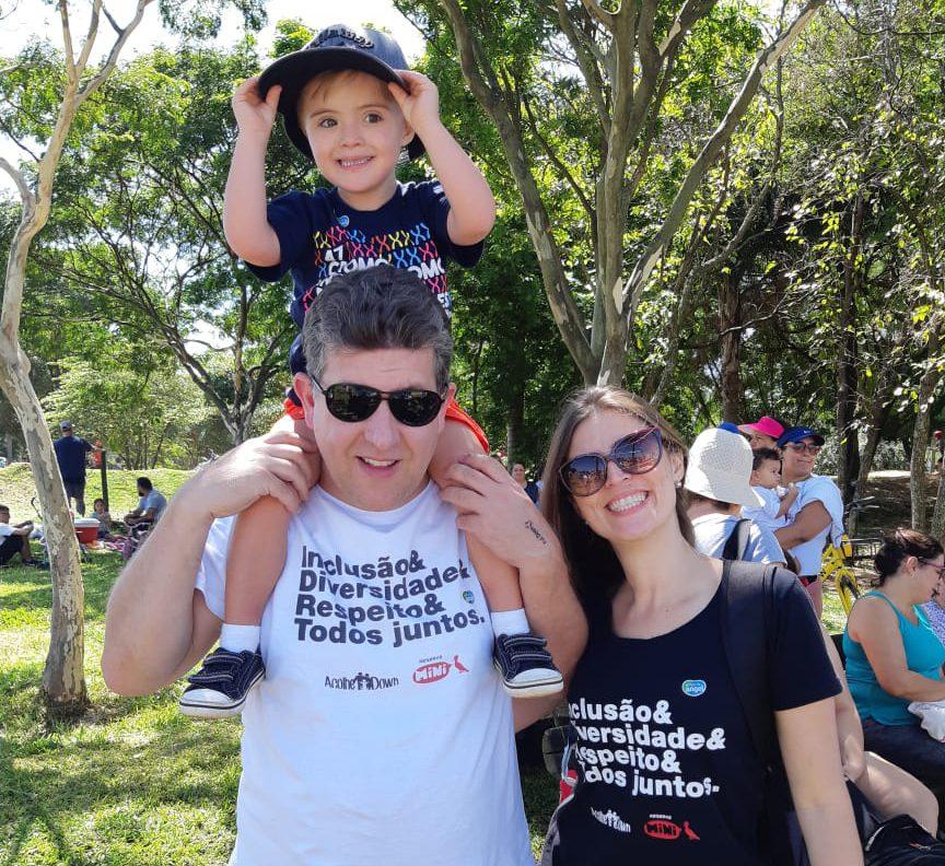 """Em parque, pais vestindo camisetas escrito """"Inclusão & diversidade & respeito & todos juntos"""". O pai leva o filho nas costas. Todos sorriem. Fim da descrição."""