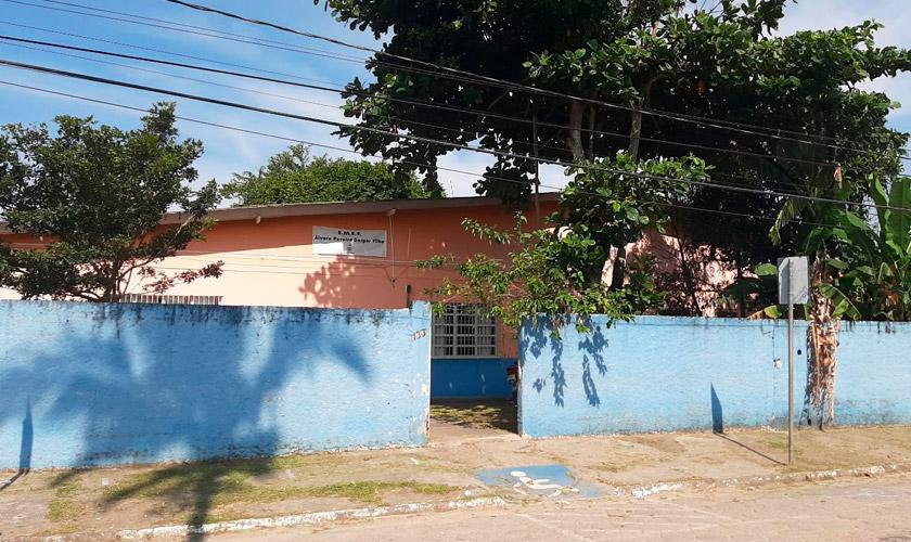 Fachada da E.M.E.F. Prof. Álvaro Pereira Gaspar Filho, com muros externos azuis e internos da cor salmão. Fim da descrição.