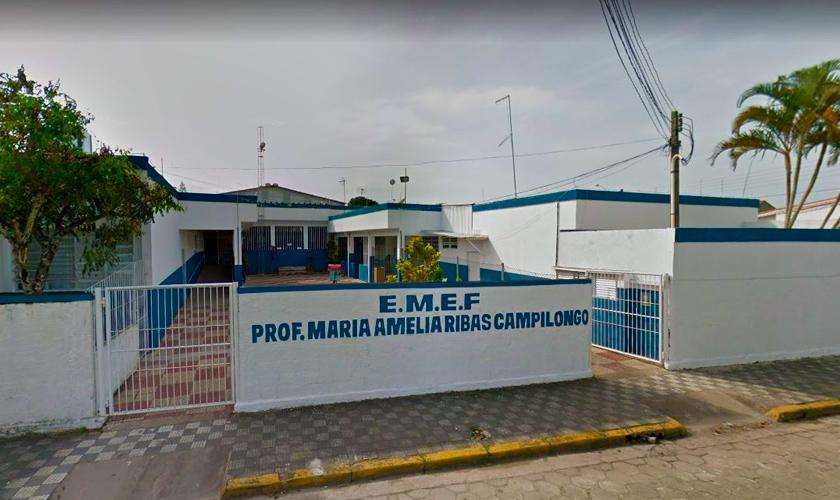 Fachada da escola Prof. Maria Amelia Ribas Campilongo, em Peruíbe (SP). a Escola possui muros brancos com detalhes em azul. Fim da descrição.