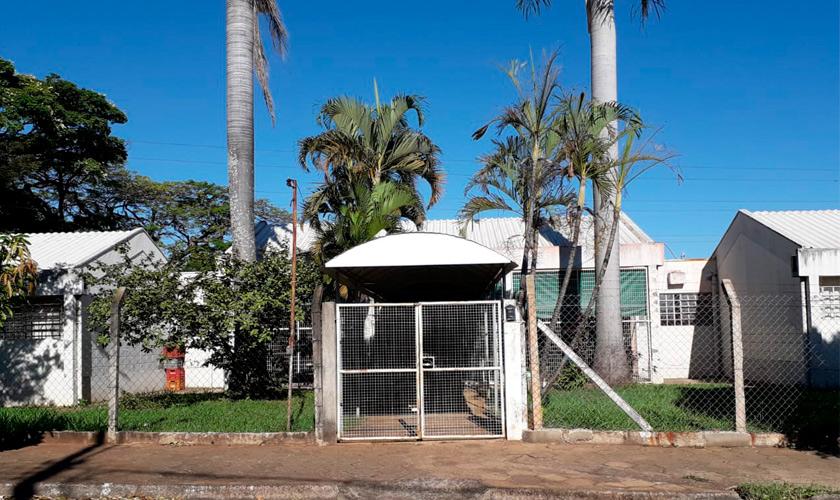 Fachada da escola de educação infantil Casa da Criança Maíra, com portões brancos. Fim da descrição.