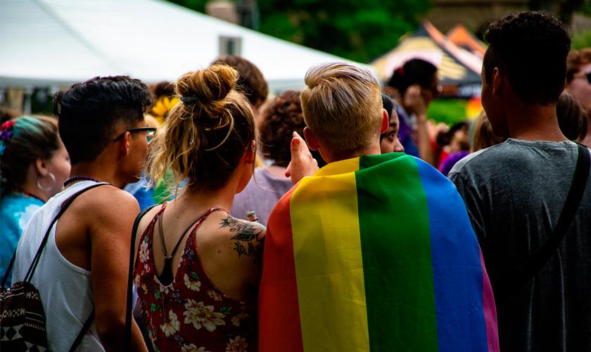 Quatro pessoas estão de costas e olham para frente. Uma delas leva uma bandeira com as cores do arco-íris. Fim da descrição.