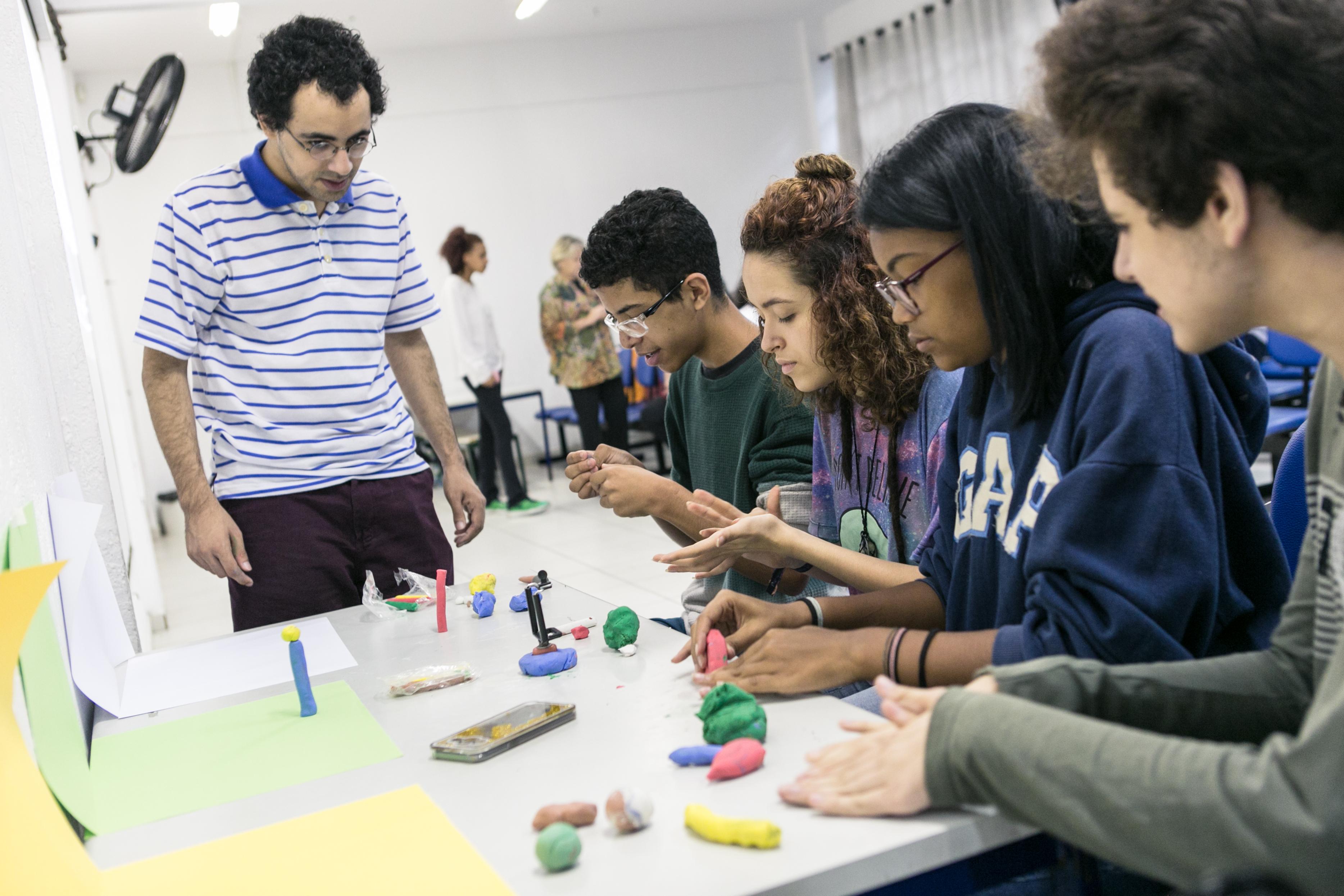 Em sala de aula, um estudante em pé observa outros quatro sentados à mesa durante realização de atividade com massa de modelar. Fim da descrição.