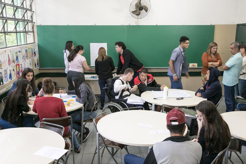 Estudantes estão em grupos sentados à mesa na sala de aula, enquanto professor e familiares estão em pé observando. Fim da descrição.
