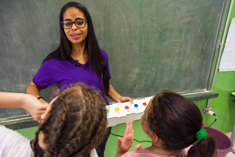 Em sala de aula, professora conversa com duas alunas enquanto segura a caixa da lousa interativa em sua mão esquerda. Fim da descrição.