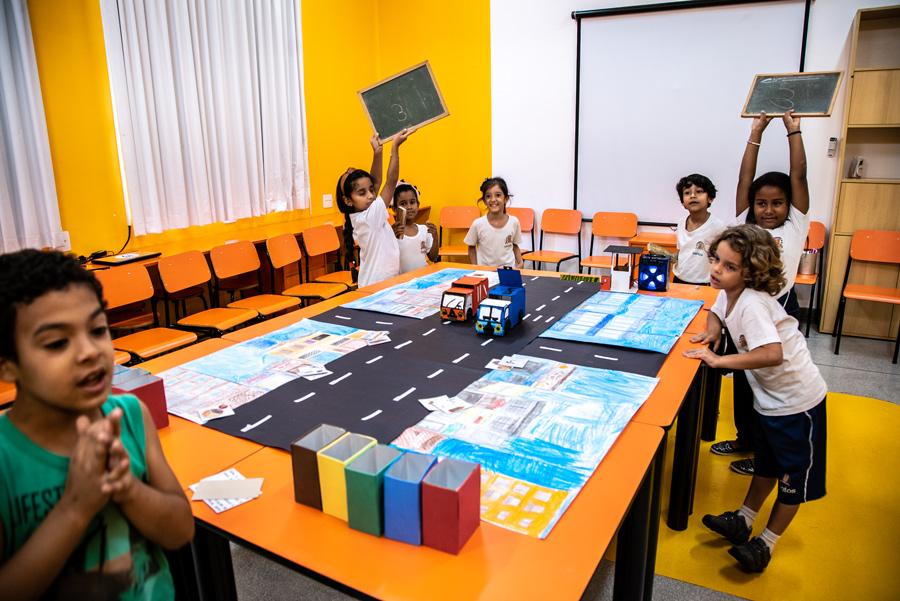 Em sala de aula, sete estudantes estão ao redor do material Caminho Sustentável. Duas estudantes levantam lousas com o número 3 escrito em giz. Fim da descrição.