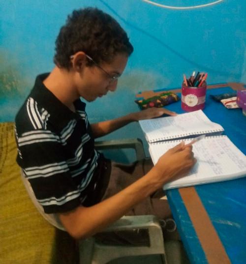 Em casa, estudante usando óculos escreve em caderno sobre mesa. Fim da descrição.