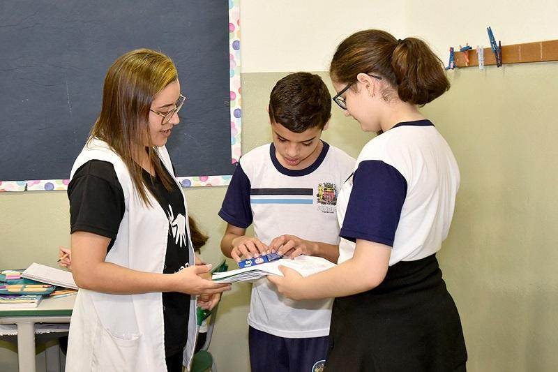 Em sala de aula, estudantes conhecem material escolar através do toque. Educadora, que está ao lado, observa a cena. Fim da descrição.