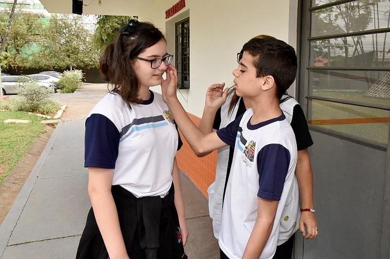 Em área aberta da escola, estudante toca o rosto da colega. Educadora, que está atrás, observa a cena. Fim da descrição.