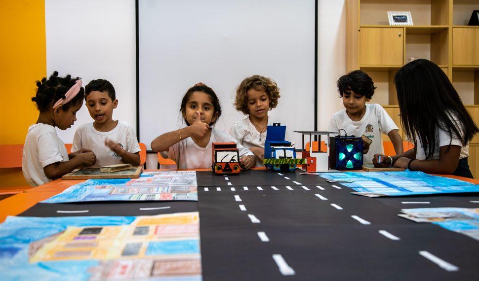 Em sala de aula e ao redor do material Caminho sustentável, seis estudantes estão divididos em pares e conversam entre si. Uma das alunas sorri e faz sinal de positivo para a câmera. Fim da descrição.