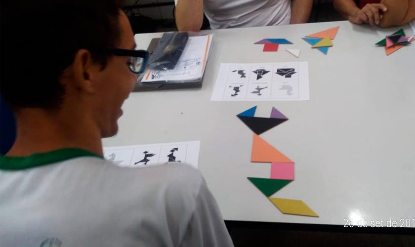 Em sala de aula, estudante usando óculos sorri enquanto olha para figura montada com formas geométricas sobre a mesa. Fim da descrição.