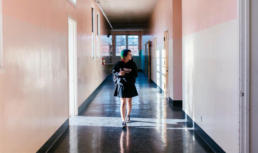 Estudante com mochila em um dos ombros anda em corredor de escola vazio. Ela usa roupas pretas, óculos e olha para a direita. Fim da descrição.