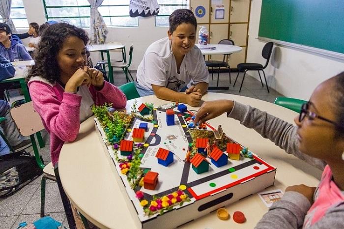 """Em sala de aula, três estudantes sorridentes interagem com material pedagógico acessível """"Jogo do Território"""". Fim da descrição."""