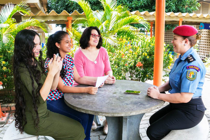 Professora Rutemara senta com duas alunas e com a Tenente Coronel Valdeane Alves em mesa redonda em área externa da escola. Fim da descrição.