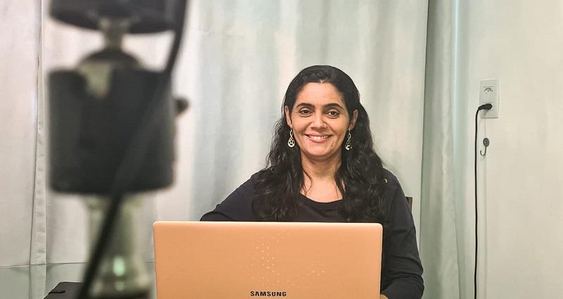 Helayne está sentada e sorri antes da gravação do tutorial. À sua frente, um notebook e a câmera para gravação do vídeo.