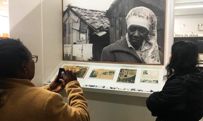 Foto de duas estudantes da EJA em uma exposição da escritora Carolina de Jesus no Museu AfroBrasil. Fim da descrição.
