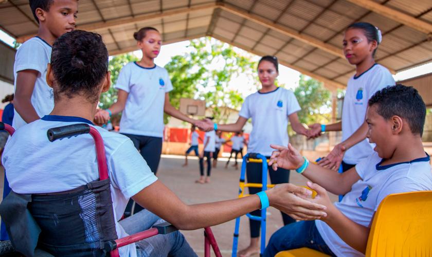Em quadra esportiva, seis estudantes uniformizados formam círculo enquanto dão as mãos. Há uma menina e um menino sentados, a menina está em cadeira de rodas. Fim da descrição.