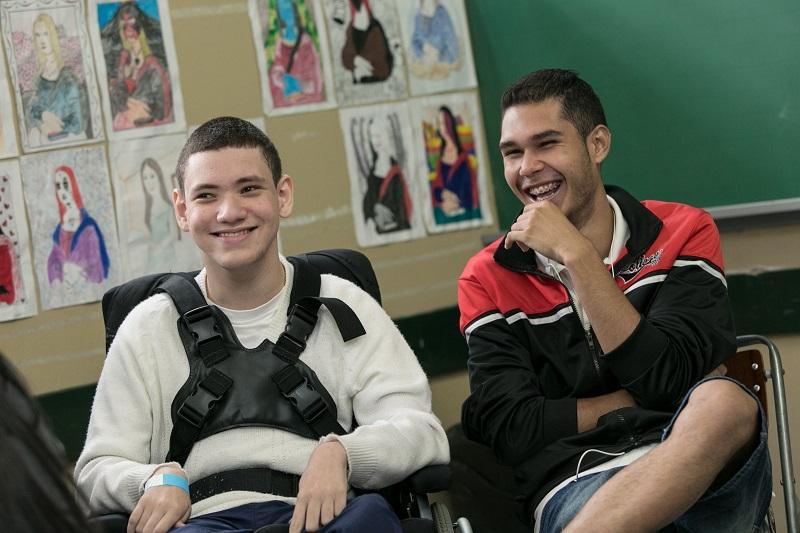 Dois estudantes sentados, sendo um em cadeira de rodas, conversam e dão risada em sala de aula. Fim da descrição.
