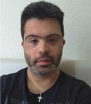 João Vitor posa para foto usando uma camiseta preta e uma corrente no pescoço, com pingente prata em formato de cruz. Ele é um homem branco na faixa etária de 30 anos, com barba, bigode e cabelo grisalhos. Fim da descrição.