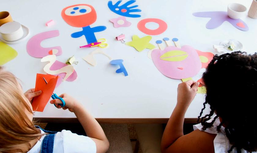 Duas meninas sentadas lado a lado recortam papéis coloridos. À frente delas, em mesa, várias figuras nas cores rosa, vermelho, azul e amarelo. Fim da descrição.