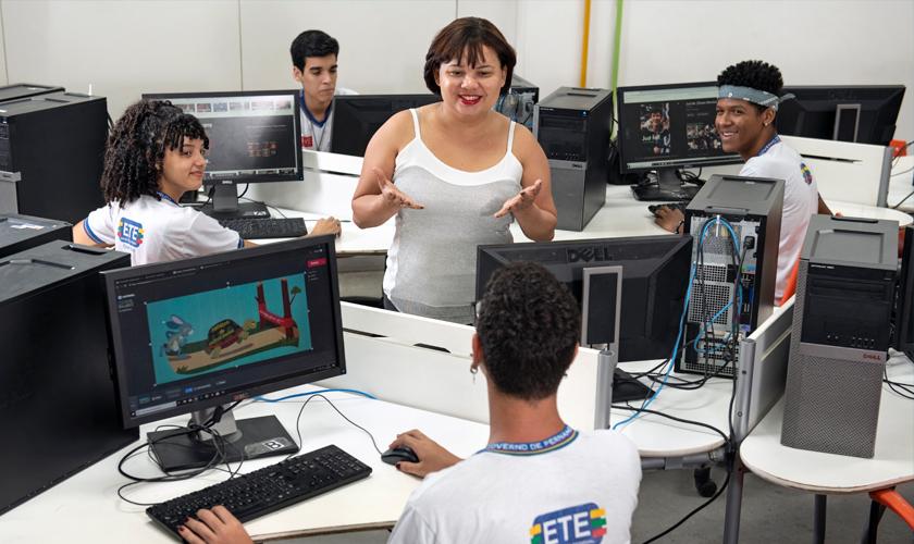 Em meio à sala de informática, educadora conversa com estudantes uniformizados. Fim da descrição.