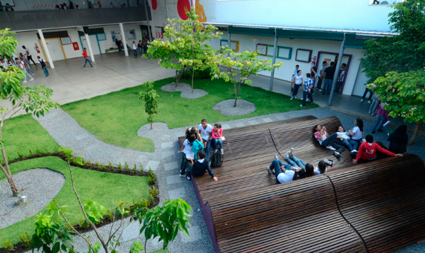 Foto tirada de cima mostra estudantes espalhados pelo pátio escolar da Escola Técnica Estadual Cícero Dias, com área verde e bancos de madeira. Fim da descrição.
