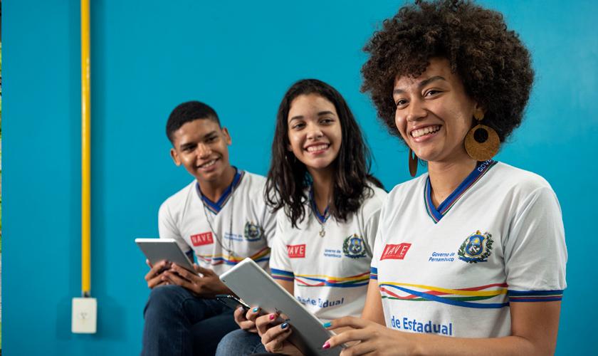 Três jovens sentados enfileirados, com tablets nas mãos. Todos vestem uniforme do Núcleo Avançado em Educação e sorriem. Fim da descrição.