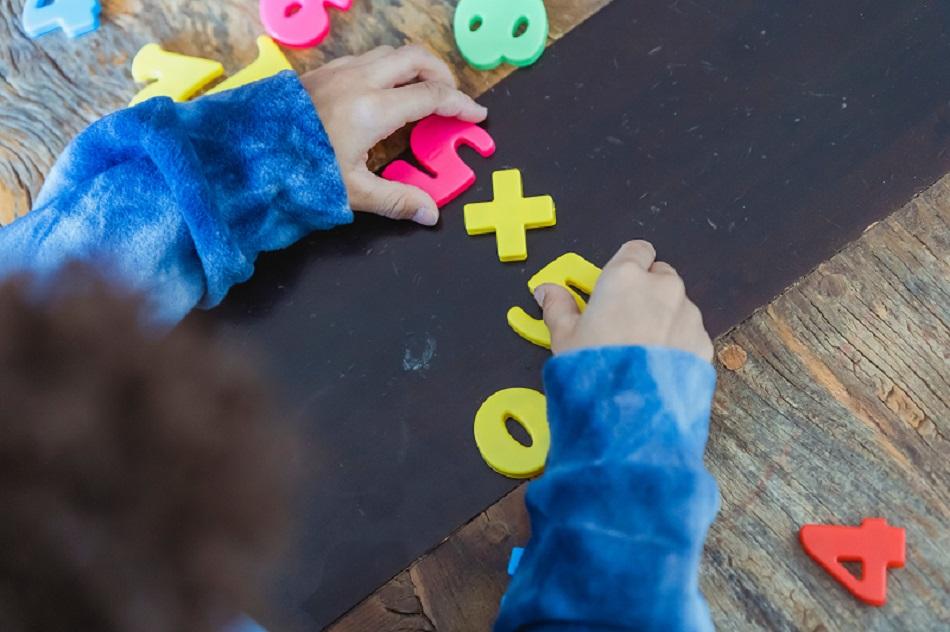 À mesa, criança utiliza material pedagógico colorido em formato de números para o aprendizado da tabuada. Ela segura sobre a mesa dois números cinco.