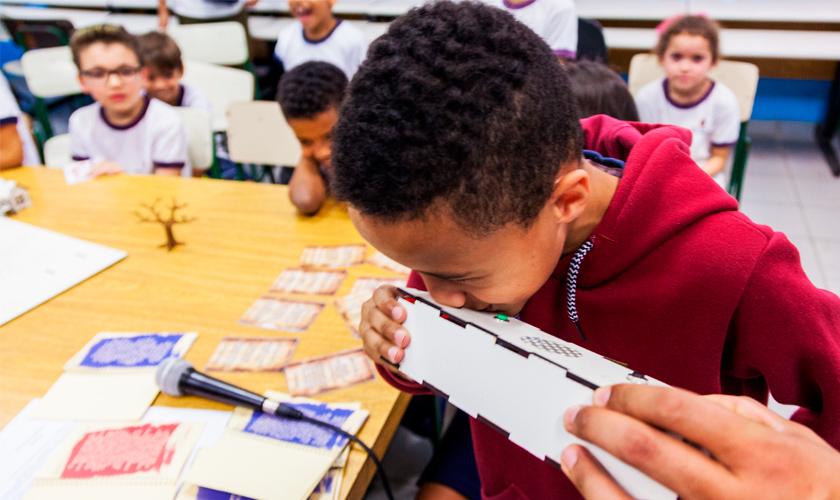 Em sala de aula, estudante assopra caixa de MDF que faz parte de material pedagógico acessível. Ao fundo, seus colegas de classe sentados em volta de mesa observam. Fim da descrição.