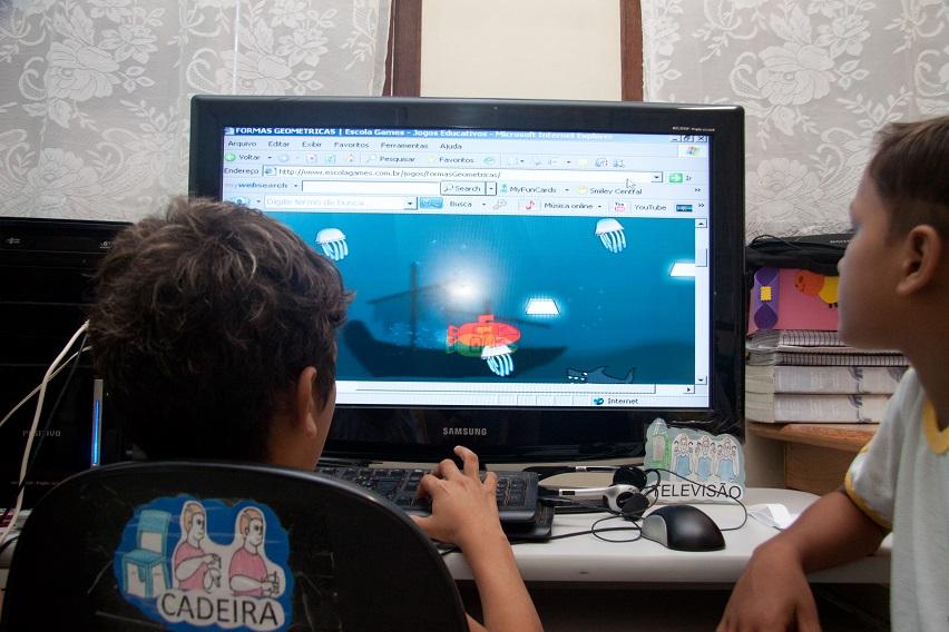 Dois estudantes estão sentados utilizando um computador para participar de um jogo educativo sobre formas geométricas. Fim da descrição.