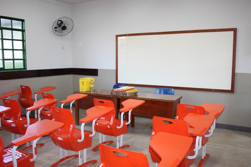 Em sala de aula, carteiras de escola na cor laranja estão vazias. À frente, uma lousa branca, mesa do professor com alguns pertences e, ao lado, um ventilador fixado na parede. Fim da descrição.