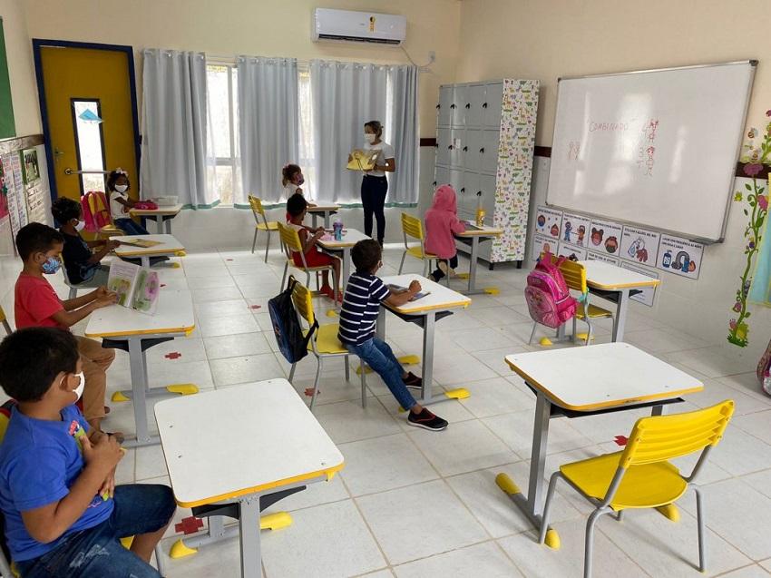 Estudantes sentados na carteira acompanham apresentação aula com professora. Todos utilizam máscaras. Fim da descrição.