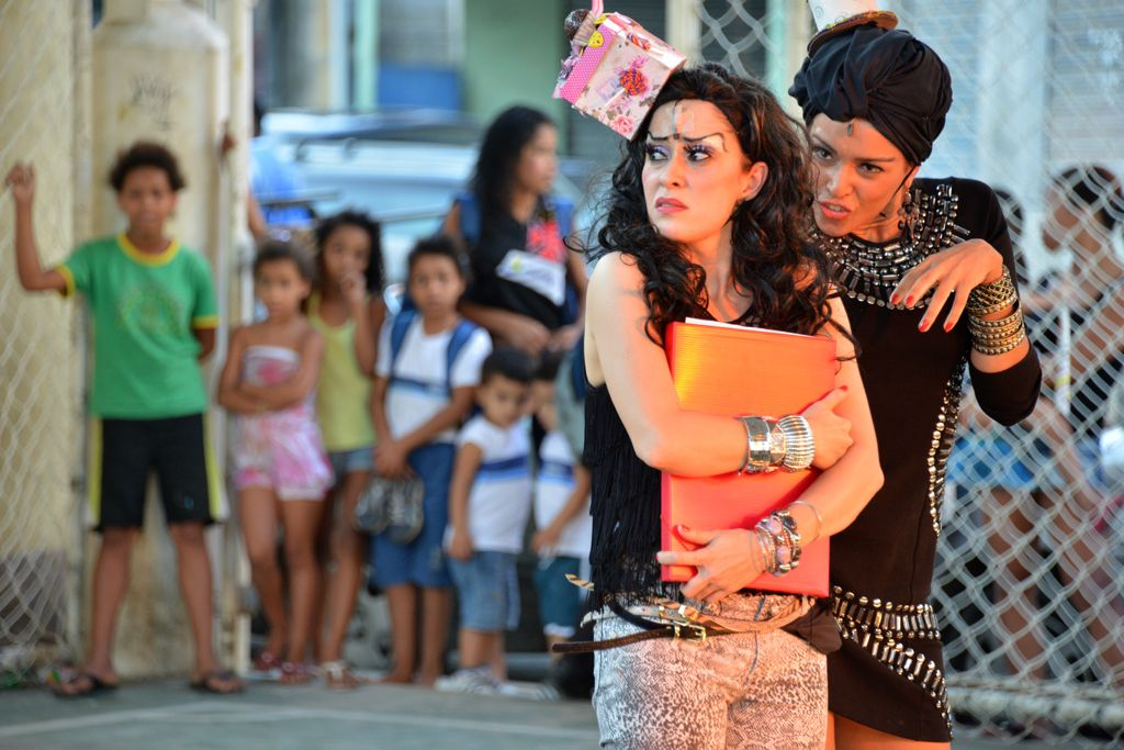 Duas atrizes contracenam em ambiente ao ar livre, sendo observadas ao fundo por algumas crianças e adultos.