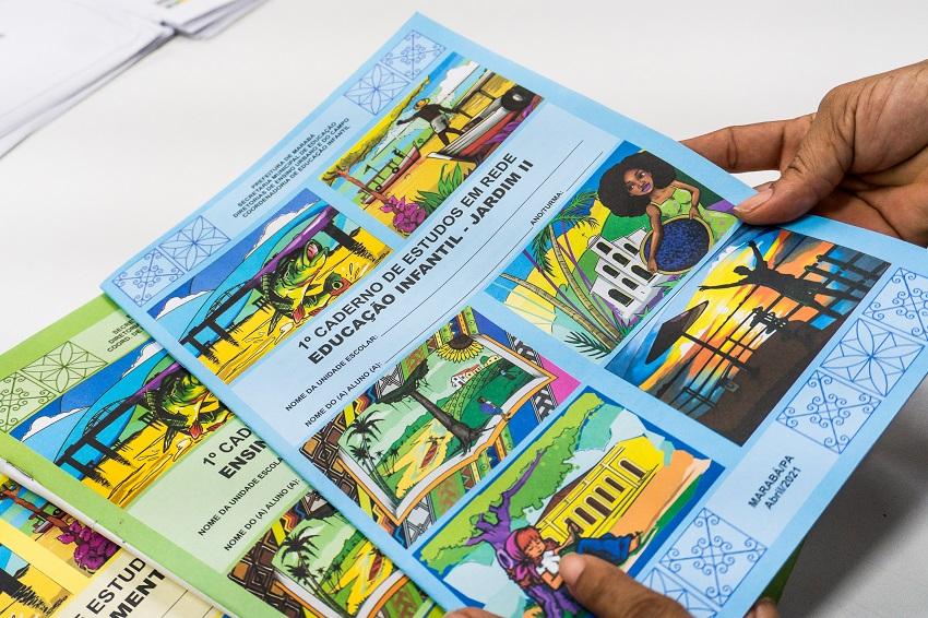 """Duas mãos seguram um caderno de estudos na cor azul e com ilustrações de Marabá, que está em cima de outros dois cadernos. Na capa do material didático está escrito """"1º caderno de estudos em rede. Educação Infantil – Jardim II"""". Fim da descrição."""
