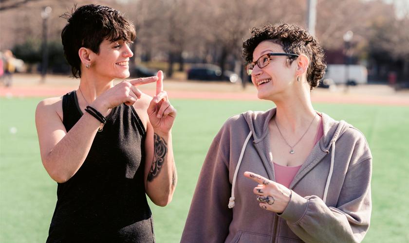 Duas mulheres adultas, com cabelo curto, fazem sinais com as mãos e sorriem uma para a outra. Fim da descrição.