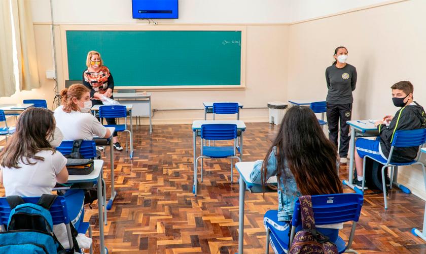 Em sala de aula, quatro estudantes utilizando máscara estão em carteiras respeitando o distanciamento social. À frente da sala, educadoras também de máscara. Fim da descrição.