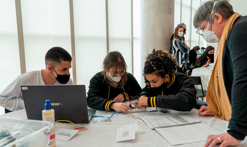 Três jovens, utilizando máscaras, estão sentados à mesa e mexem em placa com fios. Educadora, de pé ao lado de uma das estudantes, observa. Fim da descrição.