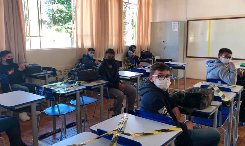 Sala de aula mostra seis estudantes usando máscara. Eles estão em distanciamento social, separados por carteiras. Fim da descrição.