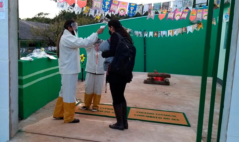 Em entrada de escola, profissionais usando máscara e faceshield conferem a temperatura de uma educadora. A escola está decorada com bandeirinhas de festa junina. Fim da descrição.